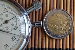 秒表和硬币与2欧元的衡量单位在木桌背景 库存图片