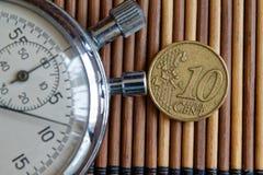 秒表和硬币与10欧分的衡量单位在木桌背景 图库摄影