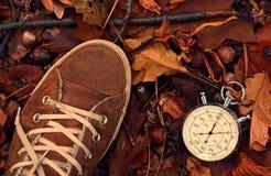 秒表和鞋子在秋天公园 库存照片