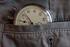 秒表,在有选项的灰色牛仔布口袋,价值措施时间,老时钟箭头分钟,第二个准确性定时器纪录 库存图片