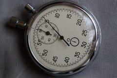 秒表,在白色牛仔布背景、价值措施时间、老时钟箭头分钟和第二个准确性定时器纪录 图库摄影
