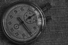 秒表,在破旧的牛仔布背景、价值措施时间、老时钟箭头分钟和第二个准确性定时器纪录 库存图片