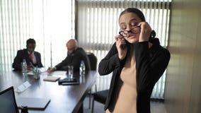 秘书在电话上时离开并且把她的玻璃放,当谈话 慢的行动 影视素材