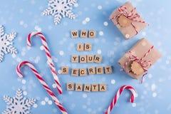 秘密圣诞老人圣诞节比赛 有笔记棒棒糖的被包裹的礼物盒在蓝色淡色背景顶视图copyspace 从lett的文本 图库摄影