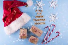 秘密圣诞老人圣诞节比赛 礼物交换 有笔记棒棒糖的被包裹的礼物盒在蓝色淡色背景顶视图copyspace 免版税图库摄影