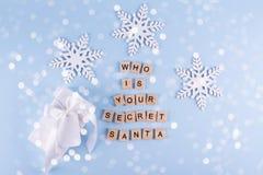 秘密圣诞老人圣诞节比赛 礼物交换 有笔记雪花的被包裹的白色礼物盒在蓝色淡色背景顶视图copysp 库存图片