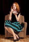 秘密地吃蛋糕的红头发人女孩。 图库摄影