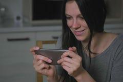秘密地打在手机的美丽的年轻女人比赛在厨房里在晚上 库存照片