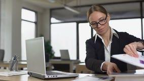 秘密地读杂志的年轻女人在办公室,避免工作的懒惰雇员 股票视频