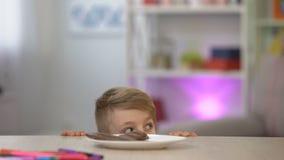 秘密地采取从白色板材的男小学生巧克力在桌,甜点心上 股票录像