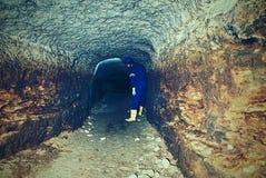 秘密工作 一个蓝色整体和安全帽的弯成拱状的工作者在隧道站立 库存照片
