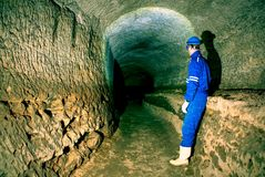 秘密工作 一个蓝色整体和安全帽的弯成拱状的工作者在隧道站立 免版税库存照片