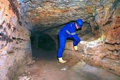 秘密工作 一个蓝色整体和安全帽的弯成拱状的工作者在隧道站立 免版税库存图片
