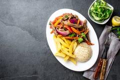 秘鲁盘Lomo saltado -牛里脊肉用紫洋葱,黄色辣椒,蕃茄在白色板材,板岩服务 免版税库存图片