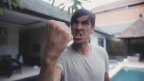 积极的人尖叫并且威胁与拳头以房子为背景在他的围场 暴力威胁  股票视频