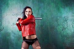 积极的低劣的妇女罢工某人有一根棒的,在红色皮夹克 免版税库存照片