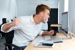 积极的愤怒的商人呼喊和与计算机一起使用在办公室 免版税库存图片