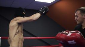 积极的拳击手与有他的教练的拳击爪子一起使用在圆环 实践的一系列的腿拳打 赤裸上身 影视素材