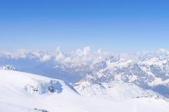 积累在多雪的山峰之间的积云在瑞士阿尔卑斯山脉 库存照片