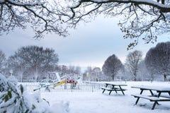 积雪的儿童操场在树丛公园 库存照片