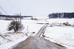 积雪的农场和绵延山路和看法,在杰夫附近 免版税库存图片