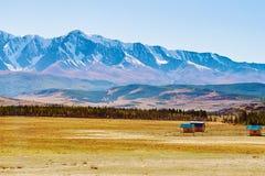 积雪的北部Chuya范围、Kurai干草原和一些个偏僻的房子的看法阿尔泰山的,西伯利亚,俄罗斯 库存照片