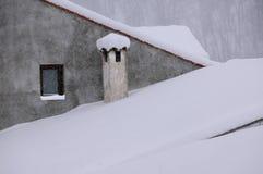 积雪的屋顶和烟囱 免版税库存照片