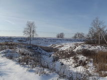积雪的山沟接近雨的土墩 免版税库存照片