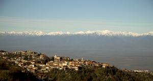 积雪的山脉背景的镇  免版税库存图片