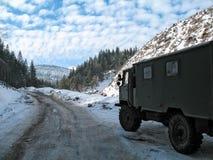 积雪的山路在与卡车的冬天 免版税库存照片