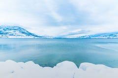 积雪的岩石和山在欧肯纳根湖 免版税库存照片