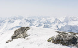积雪的岩石有在后面的山景 免版税库存照片