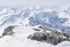 积雪的岩石有在后面的山景 免版税图库摄影
