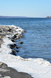 积雪的岩石海岸线晚冬、蓝天和小山 免版税库存图片