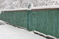 积雪的木板走道老绿色篱芭 乡下阴沉的冬日 库存照片