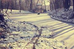 积雪的池塘和桥梁在冬天古老样式停放 免版税图库摄影