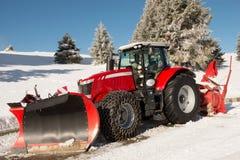积雪的清除的红色拖拉机 免版税库存照片