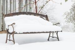 积雪的空的葡萄酒老庭院长凳在一col湿有薄雾的多雪的天 免版税库存图片