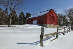 积雪的红色谷仓和分裂栅栏 库存照片
