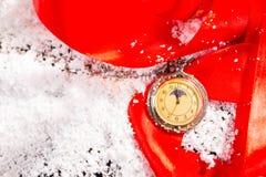 积雪的表面上的古色古香的怀表 免版税库存图片