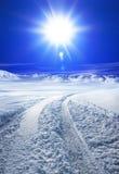 积雪的路和太阳 免版税库存照片