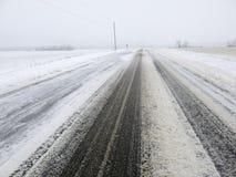 积雪的路或高速公路在冬天,行车条件 免版税库存图片