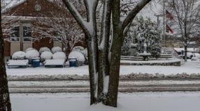 积雪的长凳和垃圾桶 库存照片