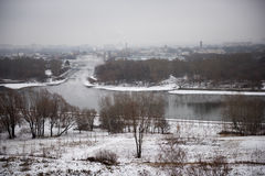 积雪的领域、树和河冬天风景在早期的有薄雾的早晨 库存图片