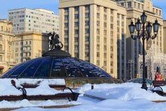 积雪的Manege广场和世界计时在俄罗斯联邦大厦杜马背景的喷泉  冬天在Mosc 库存照片