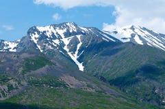 积雪覆盖的山在与日落和蓝天的夏天 库存图片