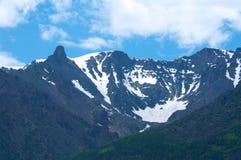 积雪覆盖的山在与日落和蓝天的夏天 免版税库存照片