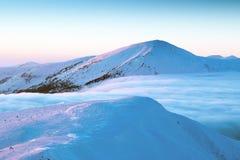 积雪覆盖的山峰,在他们中一朵蓬松云彩,寒冷,为 库存图片