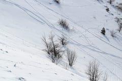 积雪覆盖的山的倾斜斑纹与滑雪轨道 免版税库存照片