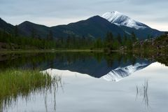 积雪覆盖的峰顶的反射在山湖 库存照片